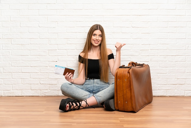 Traveler woman with suitcase and boarding pass pointing to the side to present a product