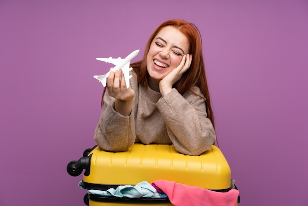 Traveler woman with a suitcase full of clothes and holding an airplane toy