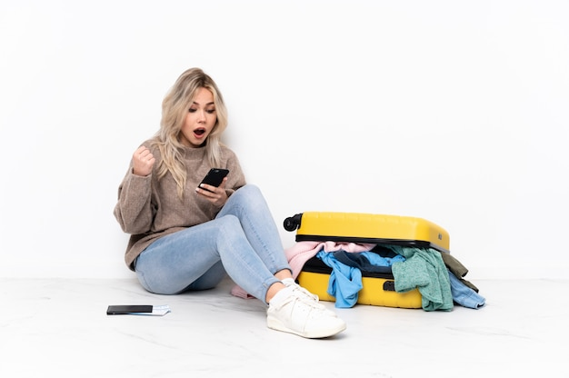 Traveler woman with a suitcase full of clothes sitting on the floor