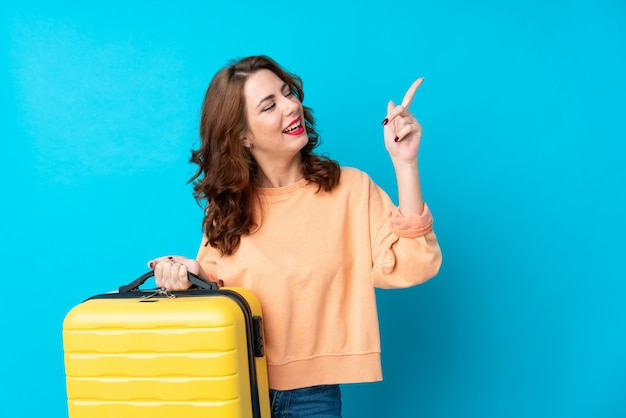 Traveler woman with suitcase over isolated blue background pointing with the index finger a great idea