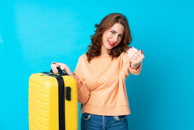 Traveler woman with suitcase over isolated blue  inviting to come