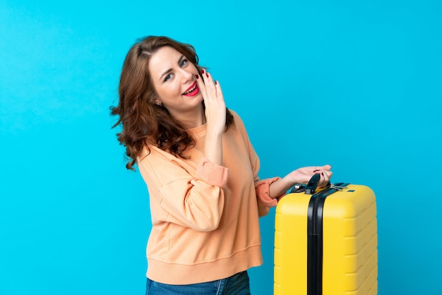 Traveler woman with suitcase over isolated  whispering something