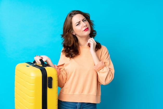 Женщина путешественника с чемоданом над изолированной голубой предпосылкой думая идея