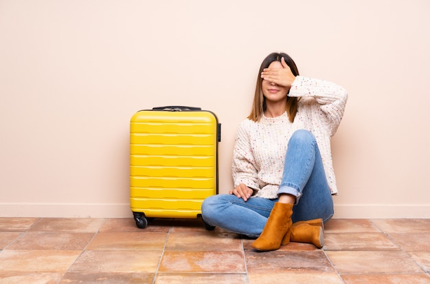 Traveler woman with suitcase sitting on the floor covering eyes by hands