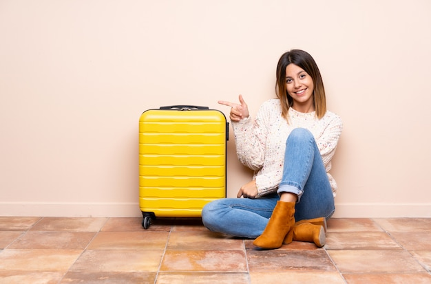 Traveler woman with suitcase sitting on the floor pointing finger to the side