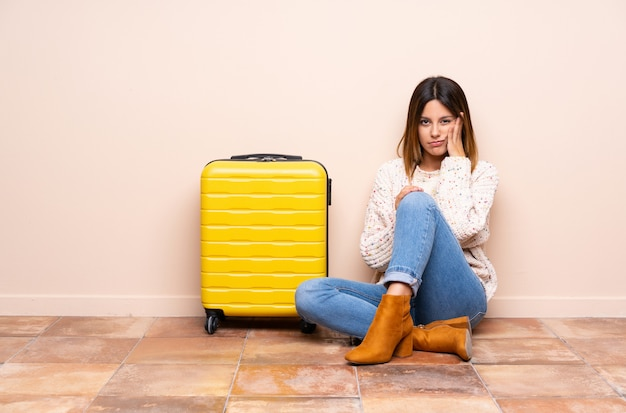 Traveler woman with suitcase sitting on the floor unhappy and frustrated
