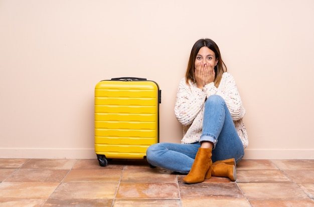 Traveler woman with suitcase sitting on the floor with surprise facial expression