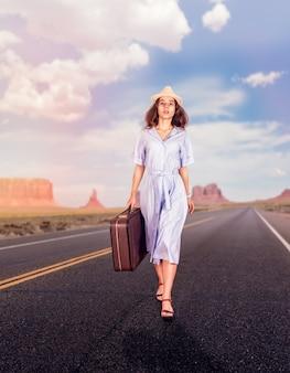 여행 가방을 들고 길을 걷고 있는 여자.