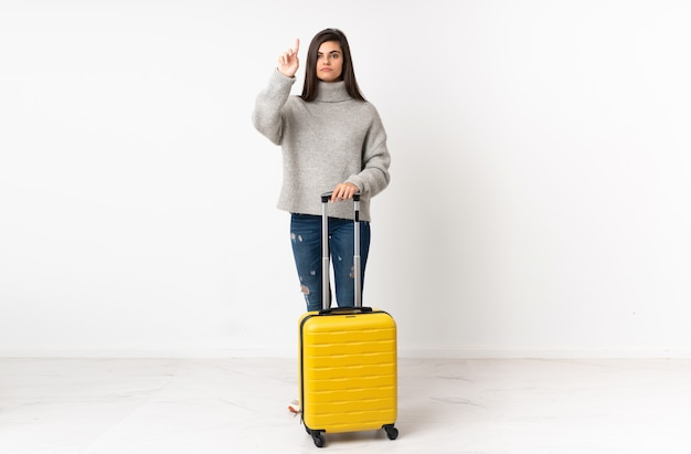 Traveler woman with a suitcase over white wall touching on transparent screen