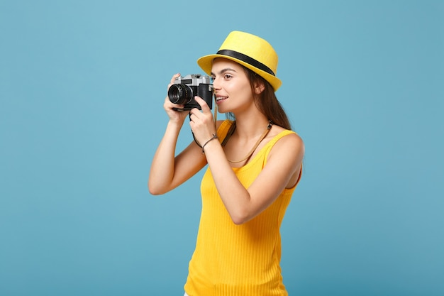 Traveler woman in yellow summer casual clothes and hat with photo camera on blue