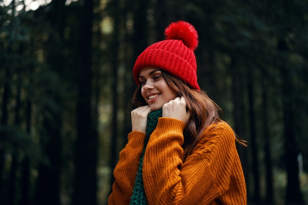 A traveler in the woods in a red hat and an orange sweater