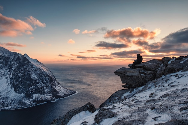 Путешественник работает с ноутбуком на горе ритен на закате на лофотенских островах, норвегия
