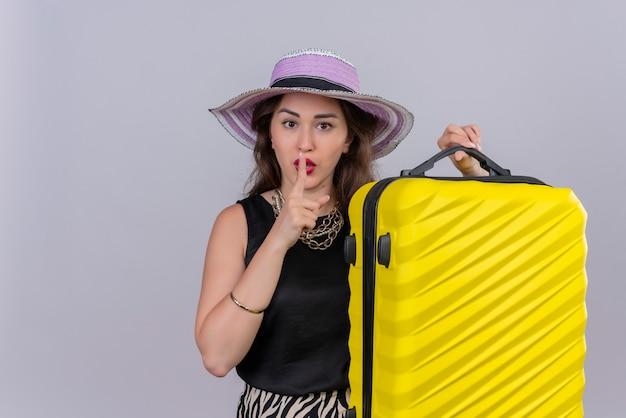 スーツケースを持って帽子に黒のアンダーシャツを着て旅行者の若い女の子と白い背景に沈黙のジェスチャーを示しています