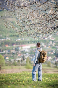 Traveler young man with backpack on hill