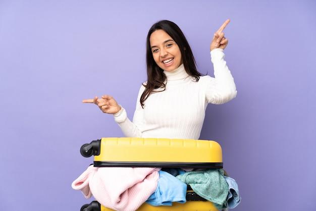 측면과 행복에 고립 된 보라색 가리키는 손가락에 옷의 전체 가방 여행자 젊은 여자