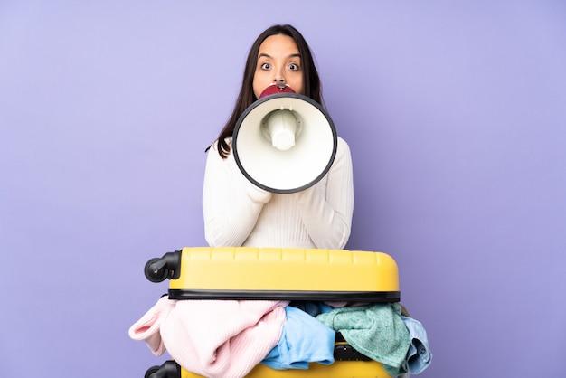 メガホンを介して叫んで孤立した紫色の服でいっぱいのスーツケースを持つ旅行者の若い女性