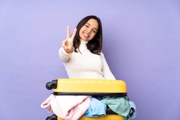 孤立した紫色の笑顔と勝利のサインを示す服でいっぱいのスーツケースを持つ旅行者の若い女性