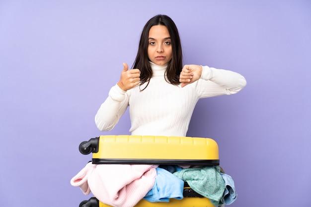 Молодая женщина путешественника с чемоданом, полным одежды на изолированном фиолетовом фоне, делая знак