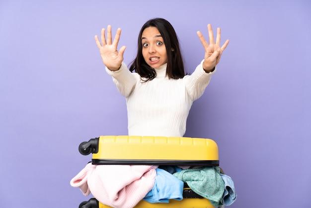 손가락으로 9를 세는 고립 된 보라색 벽 위에 옷이 가득한 가방을 가진 여행자 젊은 여자