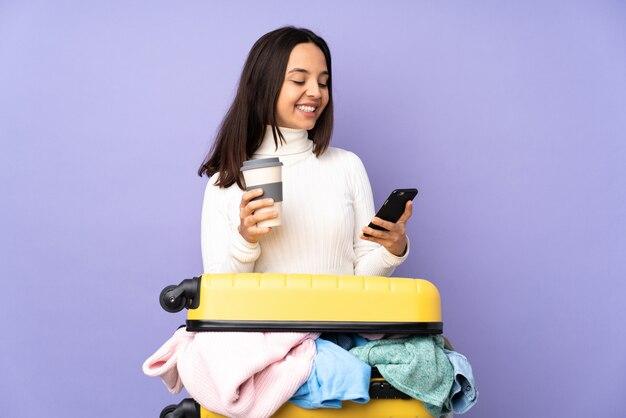 멀리 걸릴 커피와 모바일을 들고 고립 된 보라색 벽 위에 옷의 전체 가방 여행자 젊은 여자