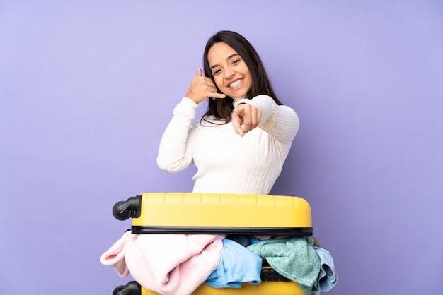 고립 된 보라색 벽 전화 제스처를 만들고 앞을 가리키는 위에 옷으로 가득한 가방을 가진 여행자 젊은 여자