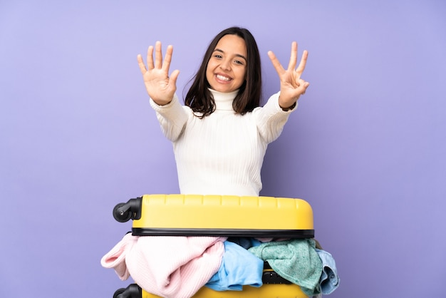 Traveler young woman with a suitcase full of clothes on isolated purple counting eight with fingers