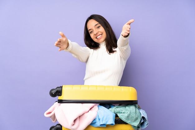 Traveler young woman with a suitcase full of clothes over purple wall presenting and inviting to come with hand