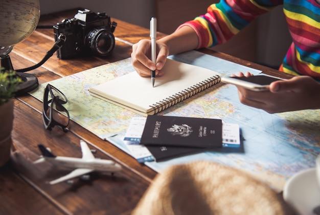여행자는지도에서 경로를 검색하고 인터넷에서 정보를 검색하여 여행을 계획하고 있습니다.