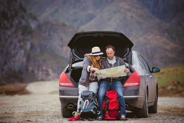 春の山を車で旅する人は地図を見る