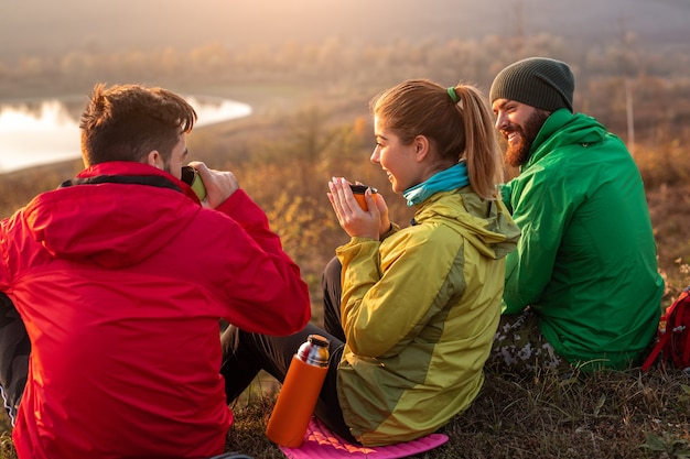 Travelers drinking hot beverage in the countryside