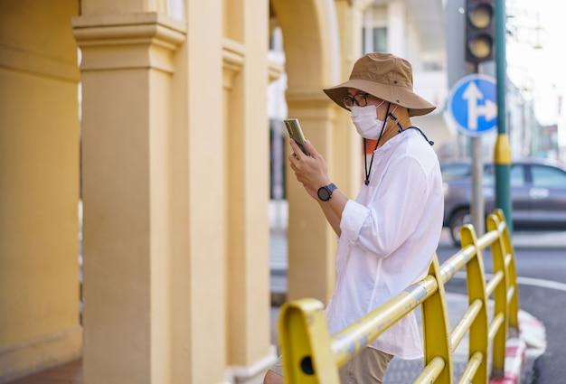 タイ、プーケットのプーケット旧市街エリアにある中葡建築建築のあるプーケット旧市街の通りを旅する旅行者。旅行のコンセプト