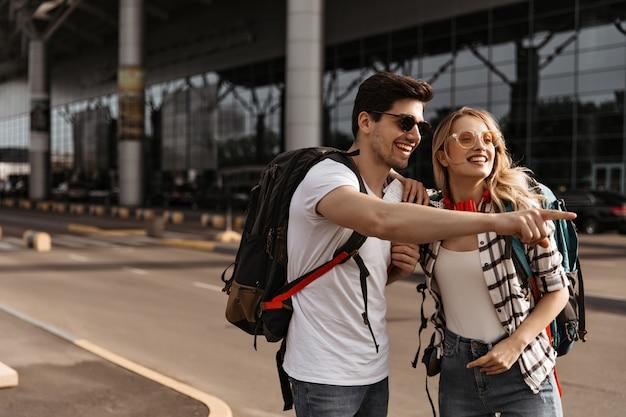 Путешественники позируют возле аэропорта в хорошем настроении