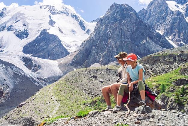 旅行者は氷河近くの丘の上の峠で休みます。素晴らしい巨大な雪山。高地でのハイキング。