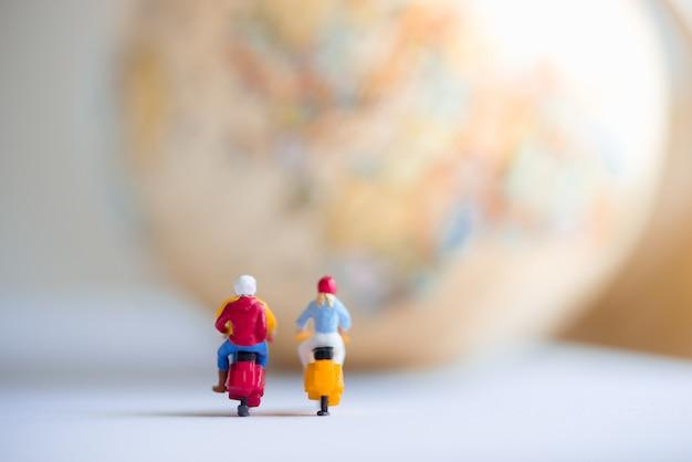 旅行や世界を探索する、低予算の旅行を使用して、地球儀でオートバイに乗る旅行者