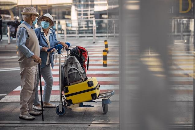 공항 터미널 입구에 서있는 여행자