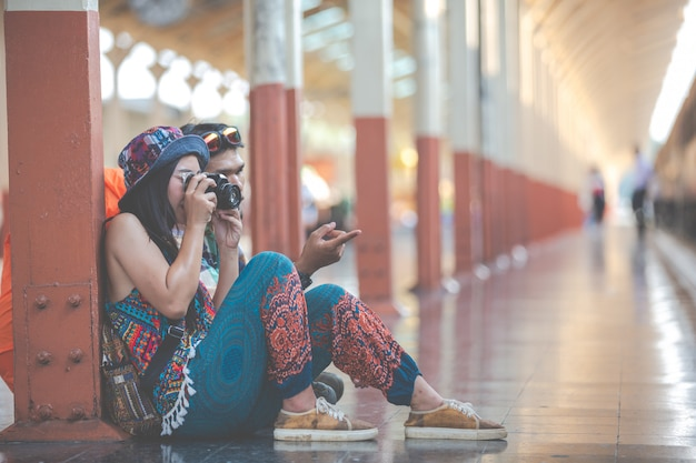 Travelers take pictures of couples while waiting for trains.