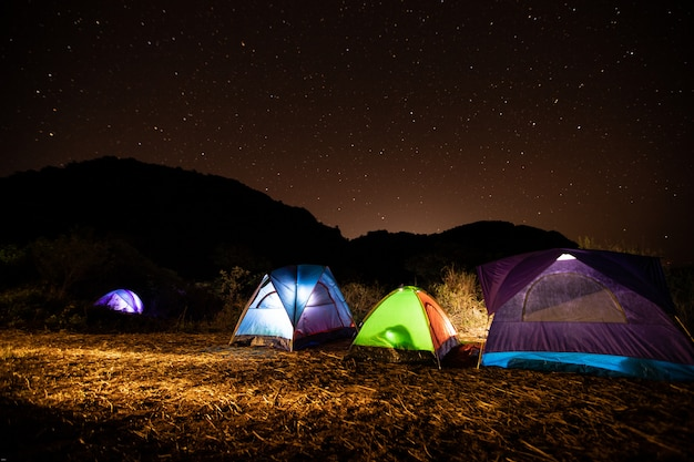 Travelers tents in the middle of the mountain at night with the stars in the sky.