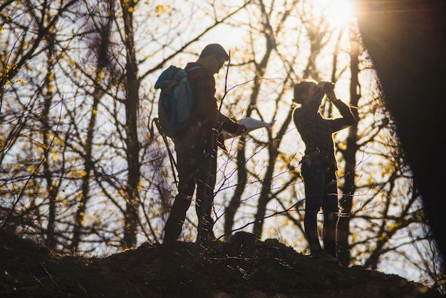 Travelers using a map and binoculars in the forest