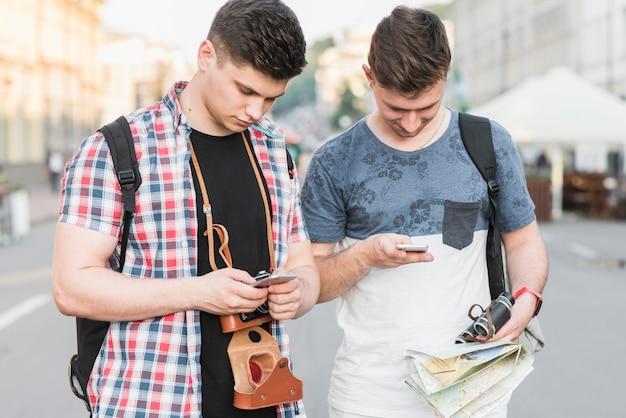 Travelers using smartphones on street