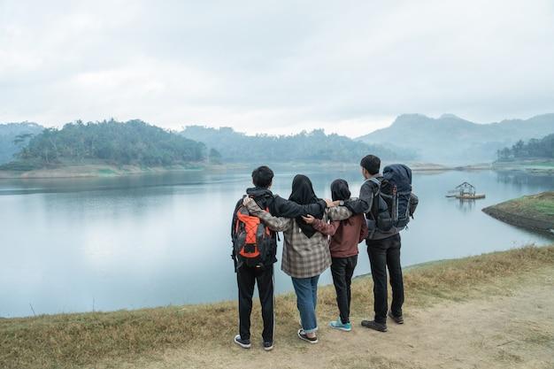 牧草地から湖の景色を見渡すバックパックを持つ旅行者