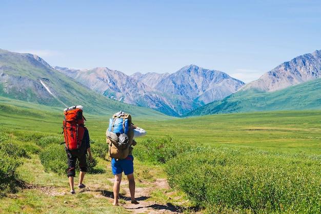 Путешественники с большими рюкзаками поднимаются по зеленой долине к гигантским горам.