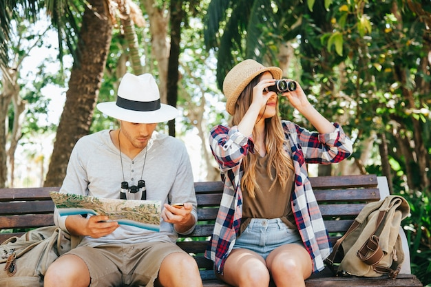 Travelers with binoculars and map