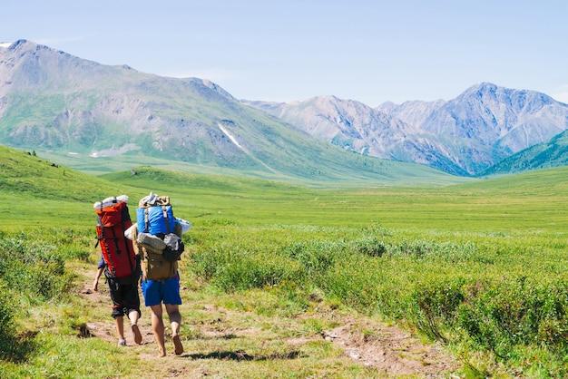 Путешественники с большими рюкзаками идут по тропинке в зеленой долине к чудесным гигантским горам со снегом. походы в горную местность. удивительный яркий горный ландшафт величественной природы.