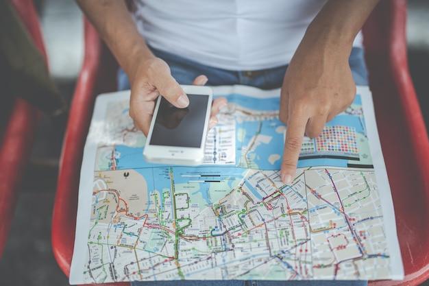 旅行者の若い女性がバックパックを見て鉄道駅で地図を保持します。観光の日。