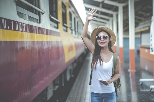 Travelers young woman with backpack looking hold tablet at the train station. tourism day