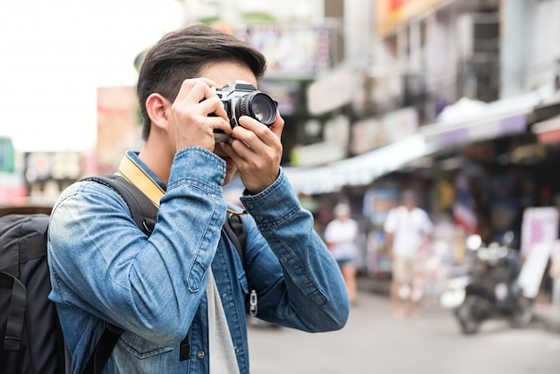 Traveling asian male tourist backpackers taking photo in khao san road,  bangkok, thailand