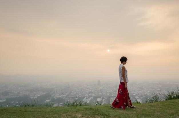 Traveling asian mature woman walking on a hilltop near a city