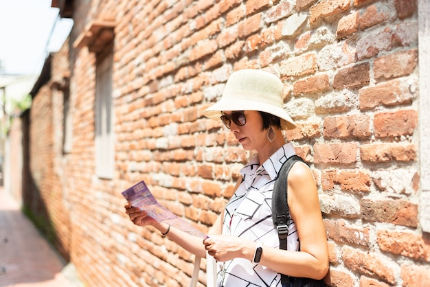 Traveling asian woman check the map in the old street at lukang town at changhua county, taiwan, asia