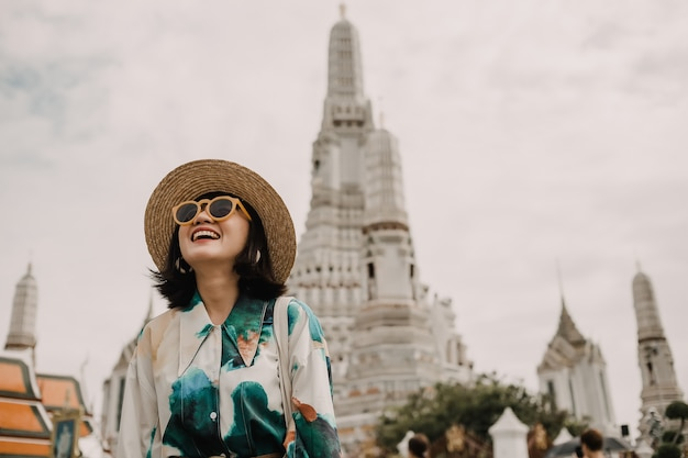 Traveling of asian woman with hat and sunglasses is standing in front of thai temple that famous place of thailand