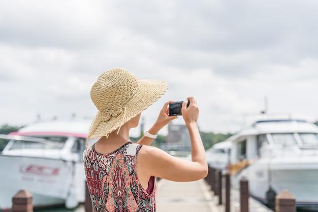 帽子をかぶった旅行中のアジア人女性が台湾の日月潭で写真を撮る